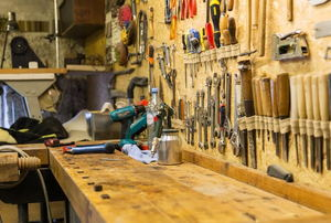 A workshop with tools hanging on the wall above a workbench.