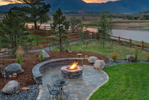 landscaped yard with fire pit area