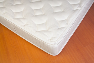 bare white mattress on laminate floor