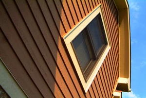 Looking up the side of a brown-sided house at its yellow eaves.