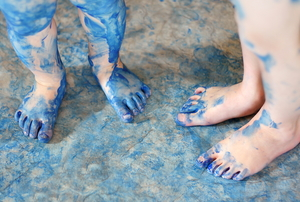 children's feet and linoleum floor splattered and stained with blue paint