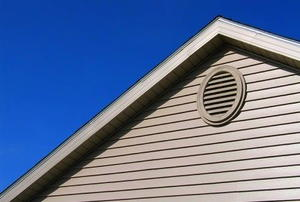 Exterior view of a gable vent on a white-sided house against a blue sky.