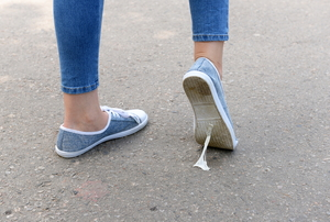 A person walking in sneakers with a piece of chewing gum stuck to their shoe.