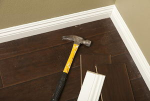 Baseboards with a hammer nearby