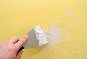 filling wall hole with putty knife and spackle