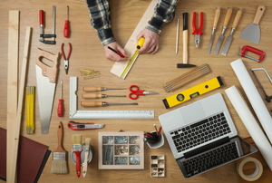 An aerial shot of a person working with a variety of tools and an open laptop.