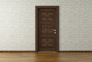 A wood door in a white brick wall.
