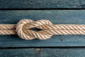 a square knot tied in a rope on wood