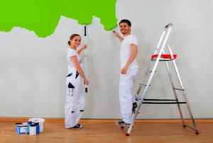 A couple painting a wall green.