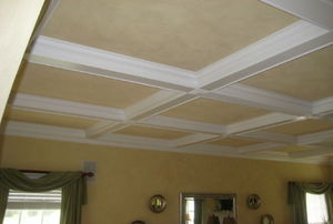 White crown molding on a tan-colored ceiling in a living room.