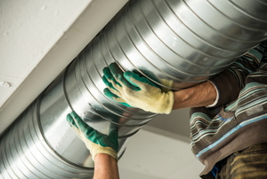 An inspection worker holding a duct.