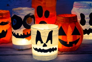 lighted halloween mason jars with colorful tissue and cutout shapes