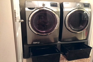 washer and dryer on pedestal with bins