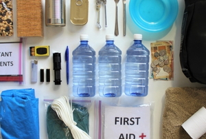 emergency items laid out neatly, including water, documents, clothes, a sleeping bag, a first aid kit, trail mix, canned food, and utensils