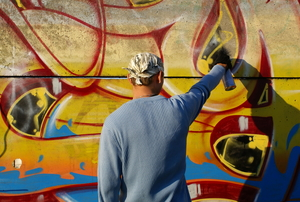 a person spraypainting a wall