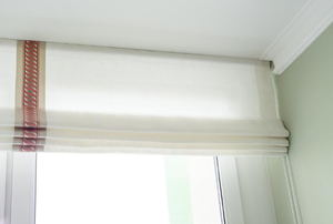 White Roman shade on a window