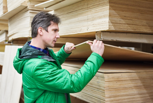 a man inspecting a stack of plywood