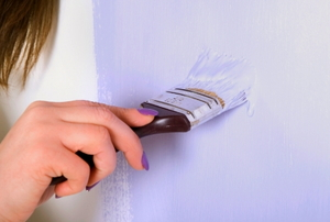A woman's hand paints a wall violet with a paintbrush.
