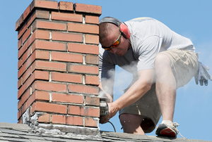 A worker performing maintenance on a brick chimney.