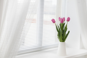 A window with white, sheer drapes and a vase of pink tulips sitting on the sill.