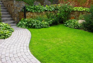 A landscaped space with a curved paver walkway and lush lawn.