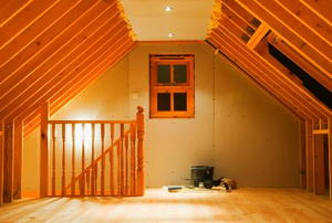 a newly finished attic with staircase and window