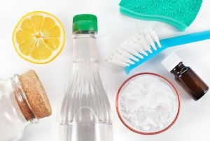 A grouping of homemade cleaning products including an essential oil bottle and a lemon.