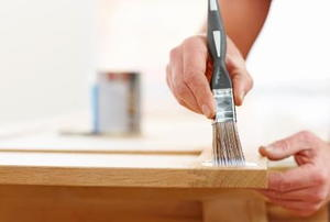A DIYer refinishing a wooden table with a paintbrush