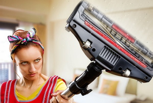 woman with broken vacuum spitting out dust