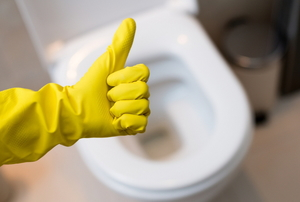 "A yellow glove giving the ""thumbs up"" sign in front of a toilet."