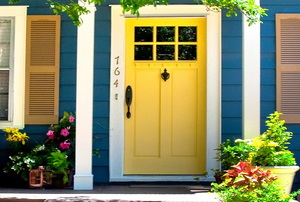 A yellow painted front door with windows.