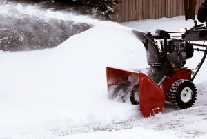 A red snowblower spitting snow off of the path.