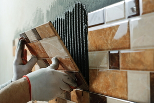 Tile being attached to a wall.
