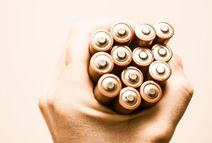a hand holding batteries