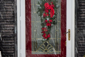 storm door with a wreath on the outside of a house in the snow