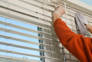 A homeowner wearing gloves and using a cloth to clean their blinds.