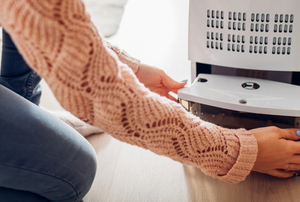 person in sweater opening the bottom of a dehumidifier
