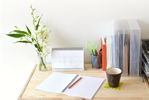 A home office desktop with files, a calendar, and a vase of flowers.