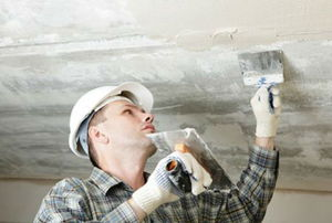 Construction worker plastering the ceiling