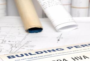 A building permit against blueprints.