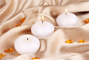 Small, white tea light candles on gold satin fabric.