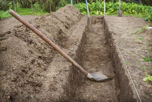 A trench with a shovel in a garden.