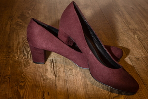 A pair of wine colored high heeled shoes made from suede.