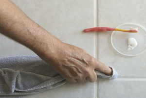A man wipes grout.