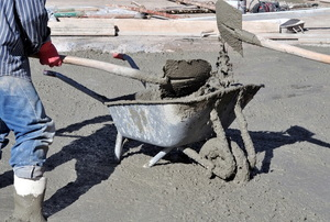 Workers mixing concrete by hand in a wheelbarrow.