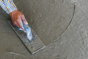 a hand smoothing out self leveling concrete