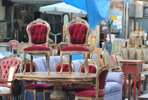 A grouping of antique and vintage furniture in a flea market.