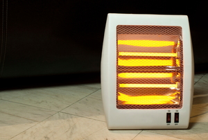 A small, electric space heater turned on to warm a tiled room.
