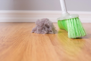 A green-bristled broom sweeping up a large dust bunny on a wood floor.