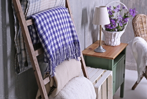 blanket ladder with blankets near wicker chair
